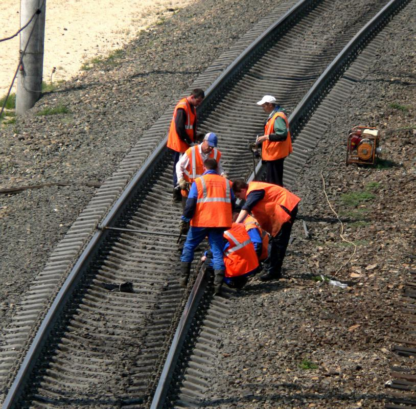 Railroad workers perform corrective maintenance on a track after a problem is uncovered.